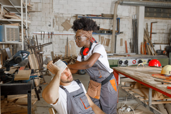 Female coworker wraps a bandage around an injured carpenter's head